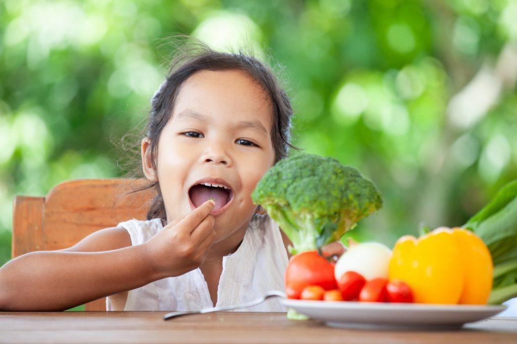 Meisje eet groentes