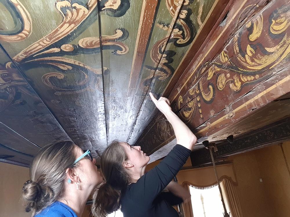 Gemeentelijk bouwhistoricus, Carolien Roozendaal, en restaurator/kleuronderzoeker Annefloor Schlotter bekijken het plafond op sporen van kleurverschillen en losse verfplekken