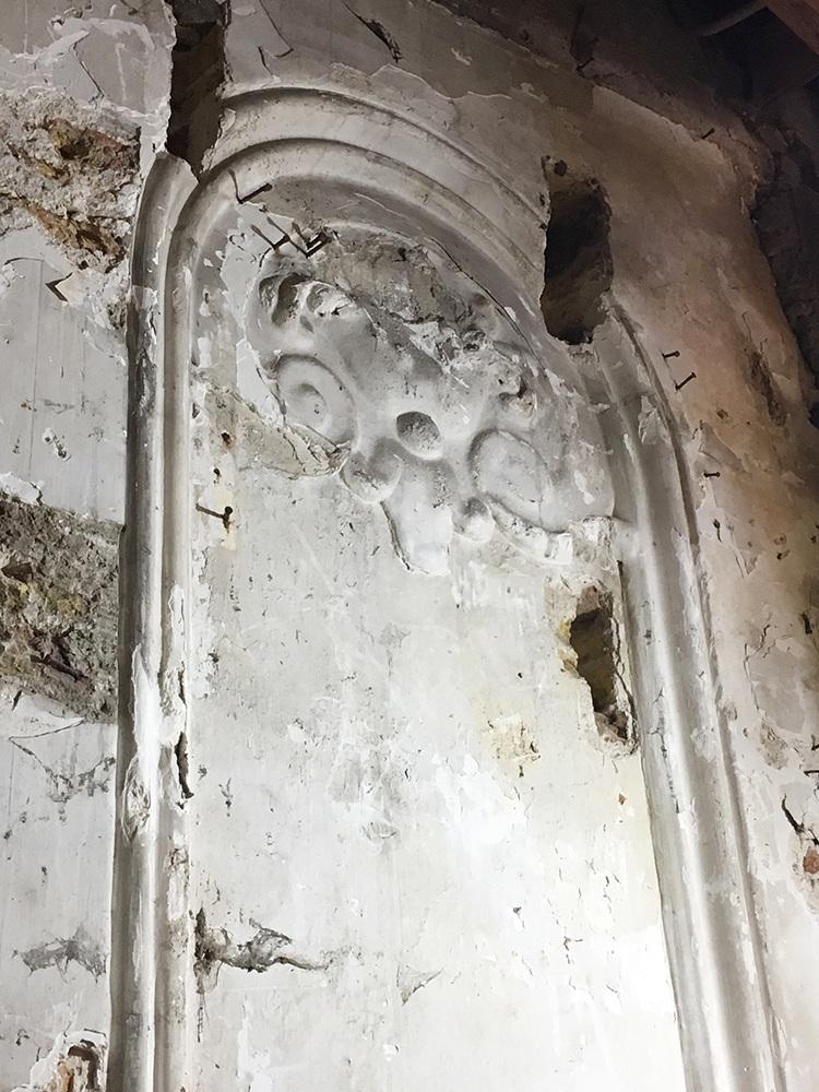 Platte en sobere krul-ornamenten in het stucwerk
