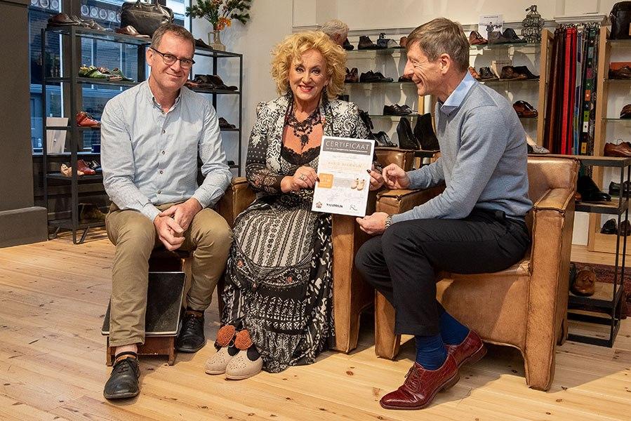 Karin Bloemen ontving het eerste paar van de handgemaakte limited edition, mét certificaat. Links meester schoenmaker René van den Berg en rechts initiatiefnemer Bert Waardijk.