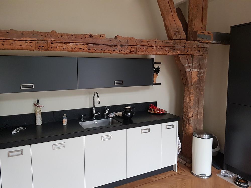 De opstelling van de moderne keuken vormt een mooi contrast met het doorleefde hout van het vierkant. Het is geplaatst tussen de vierkantstijlen en onder de jaagbalk. De korbelen zijn ook in het zicht gelaten