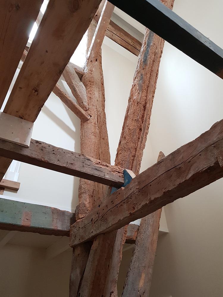 De imposante houtconstructie is over de volle hoogte onderdeel van het interieur geworden in de nieuw gevormde gang met trappenhuis