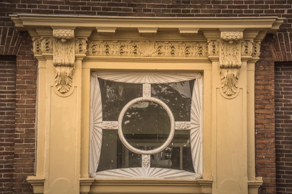 Deze rijk met houtsnijwerk versierde kroonlijst met raam is te vinden boven de voordeur van een pand aan de Bierkade 10