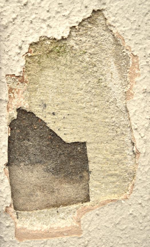 Een 'trappetje' met zeven lagen materiaal en afwerking. Van het oorspronkelijke (waarschijnlijke traskalkmortel) tot en met de laatste afwerkingslaag met gebroken witte structuurverf, zoals de meeste Alkmaarders de gevel kennen.