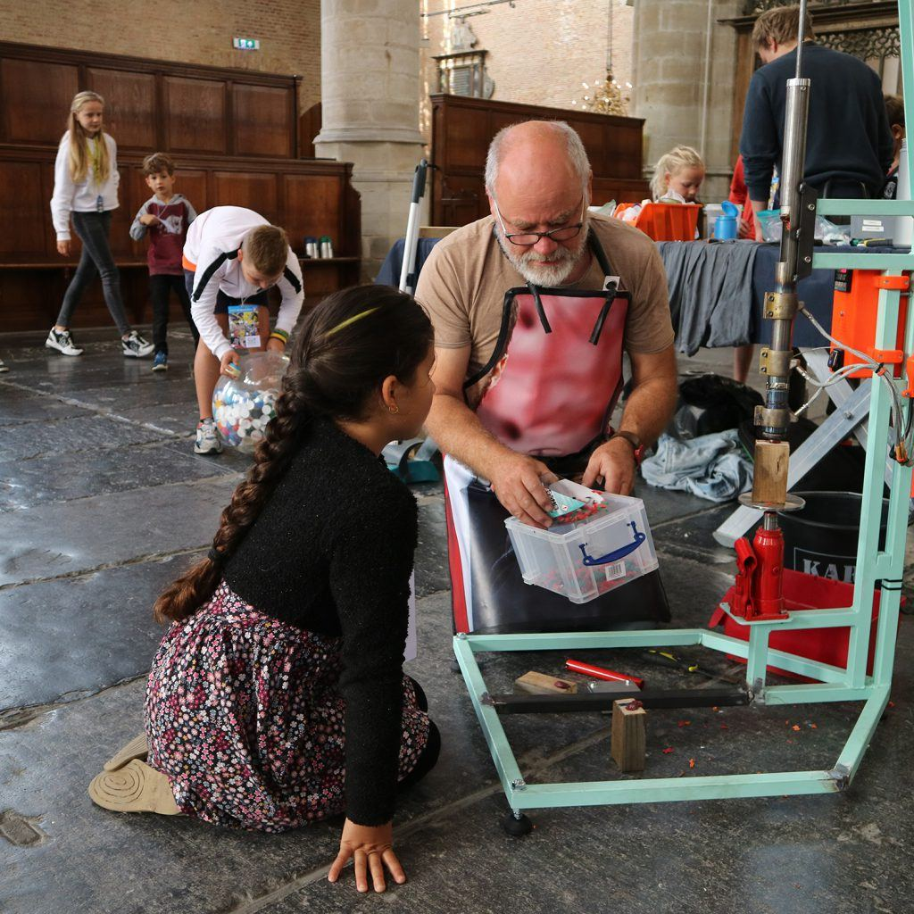 Plastic omsmelten tot munten bij de jeugdafvalmarathon in de Grote Kerk