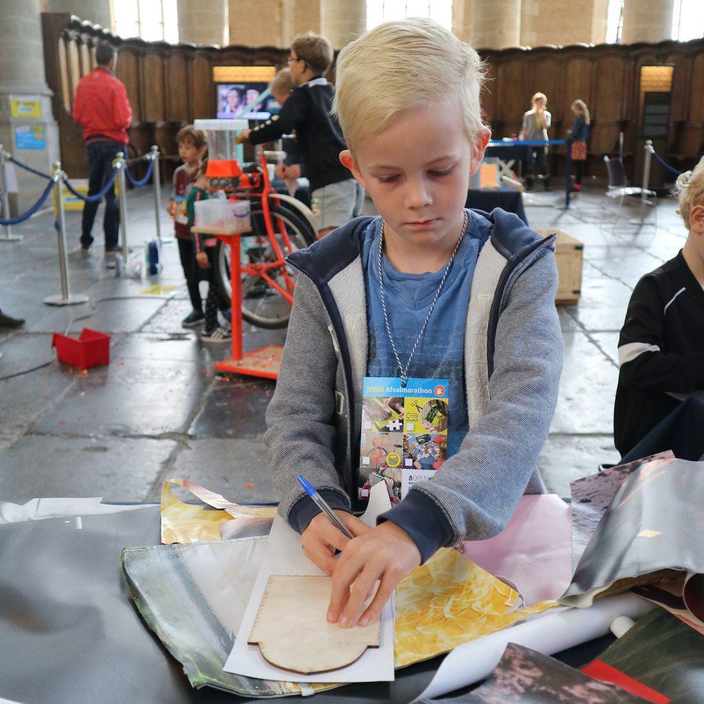 Portemonneetjes maken bij de jeugdafvalmarathon in de Grote Kerk