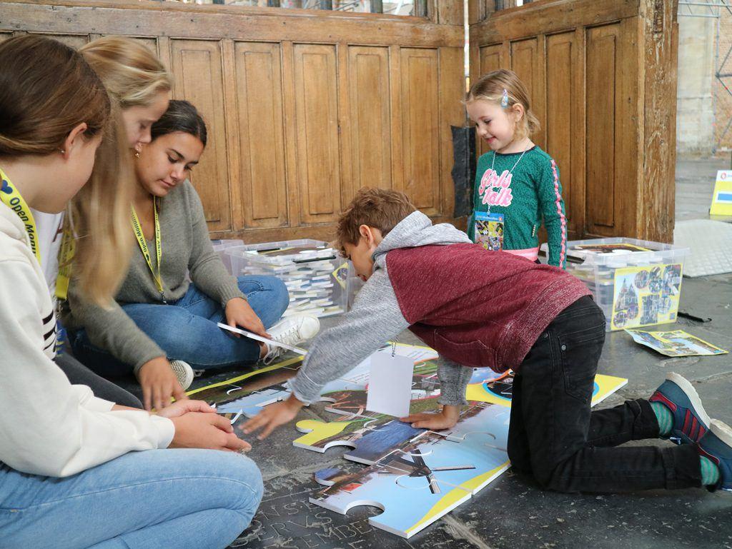 Reuzenpuzzels leggen bij de jeugdafvalmarathon in de Grote Kerk